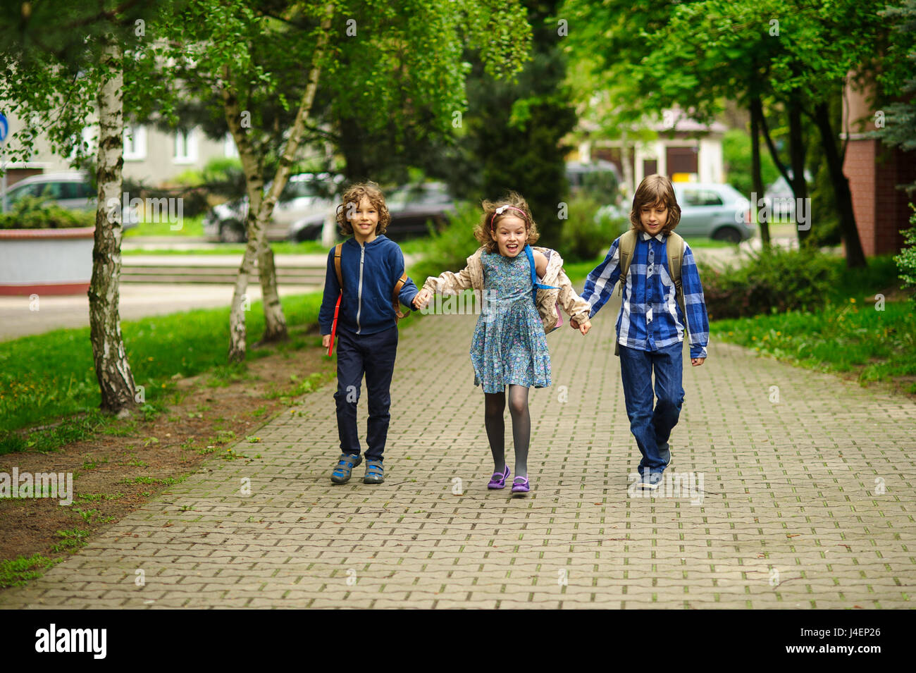 Amusing little school students go to school having joined hands. Children have an excellent mood. Behind shoulders - Stock Image
