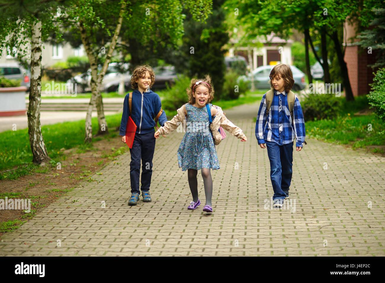 Amusing little school students go to school having joined hands. Children have an excellent mood. Behind shoulders - Stock Image