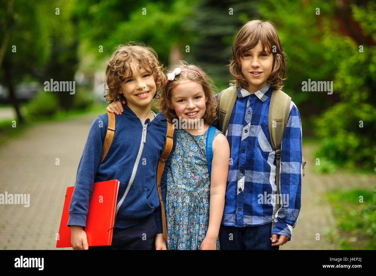 Three little school students, two boys and the girl, stand in an embrace on the schoolyard. Friends smile. School - Stock Image