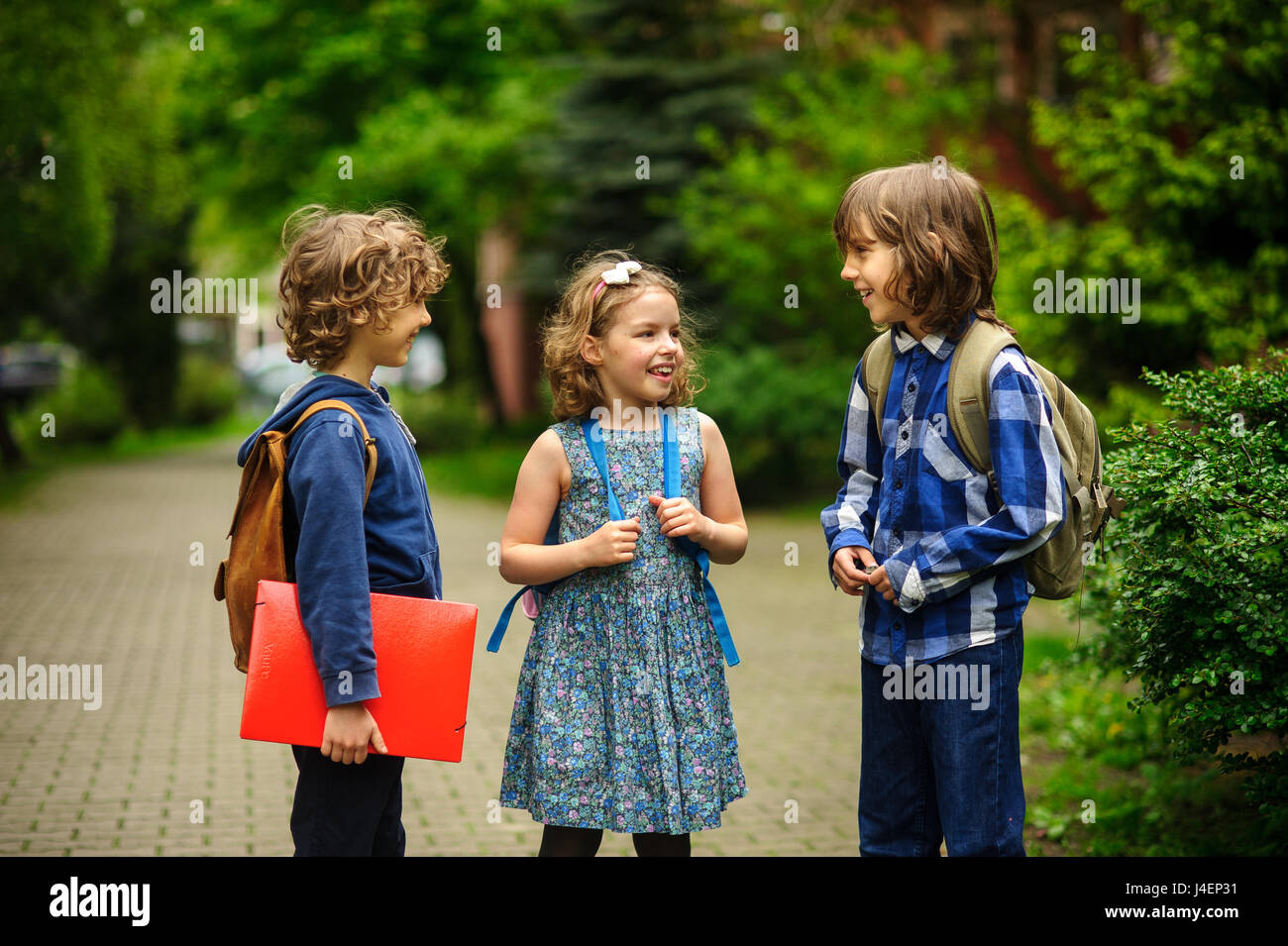 Cute little school students briskly talk on the schoolyard. Children have a good mood. Warm spring morning. Behind - Stock Image