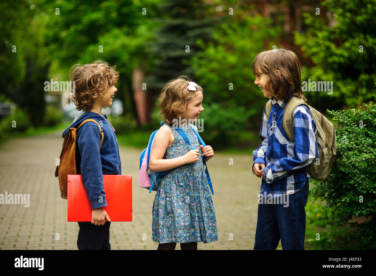 Little school students briskly talk on the schoolyard. Children have a good mood. Warm spring morning. Behind shoulders - Stock Image