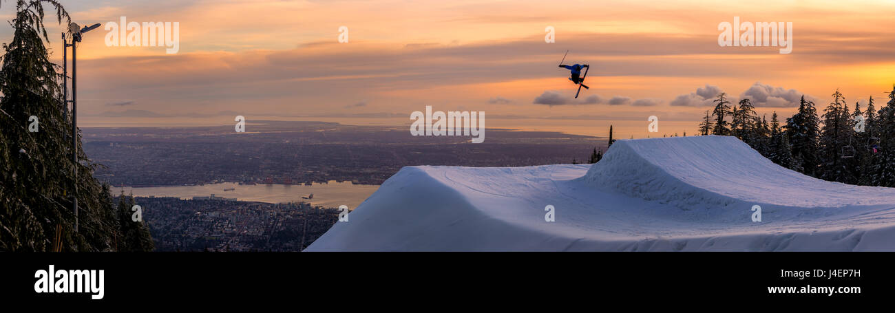 Freestyle skier doing a trick off a jump above city at sunset, Canada, North America - Stock Image