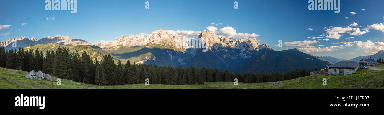Panorama of meadows and hut framed by peaks, Malga Ritorto, Madonna di Campiglio, Brenta Dolomites, Trentino-Alto - Stock Image