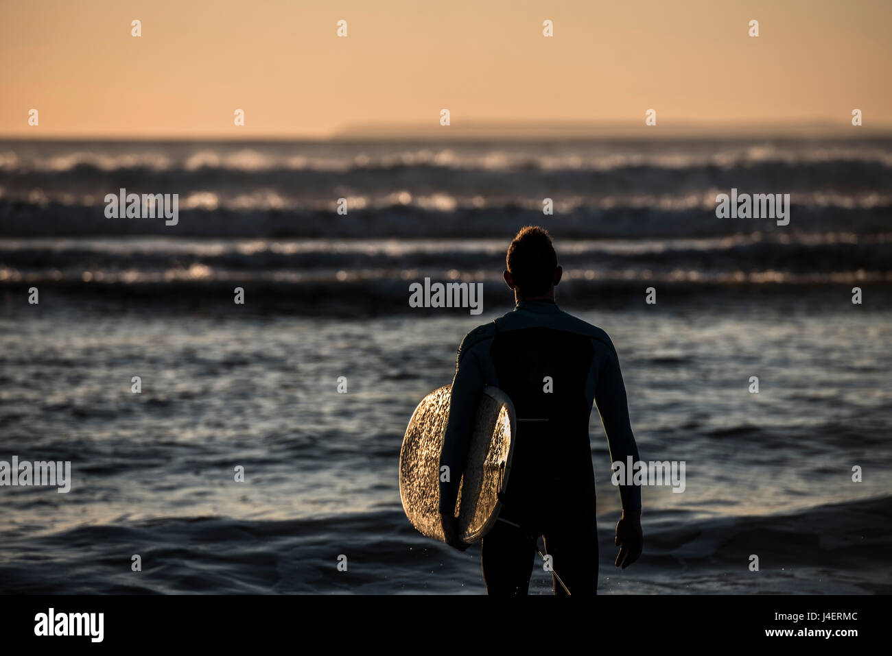 A surfer contemplating the waves at Croyde Beach in Devon, England, United Kingdom, Europe - Stock Image