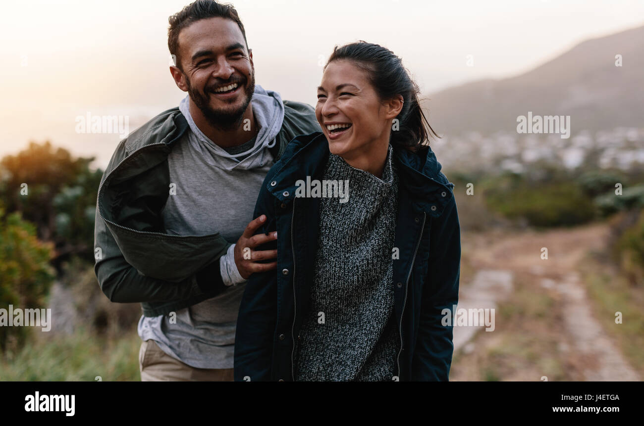 Portrait of couple walking through pathway on mountain. Man and woman enjoying vacation in countryside. Young people - Stock Image