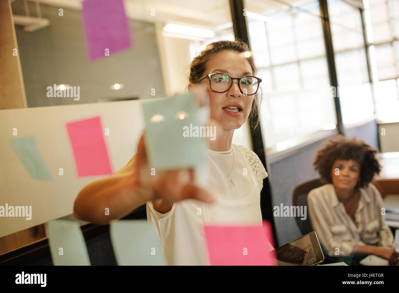 Business woman pointing at sticky note to female colleague on glass wall in office. Business people working on project - Stock Image