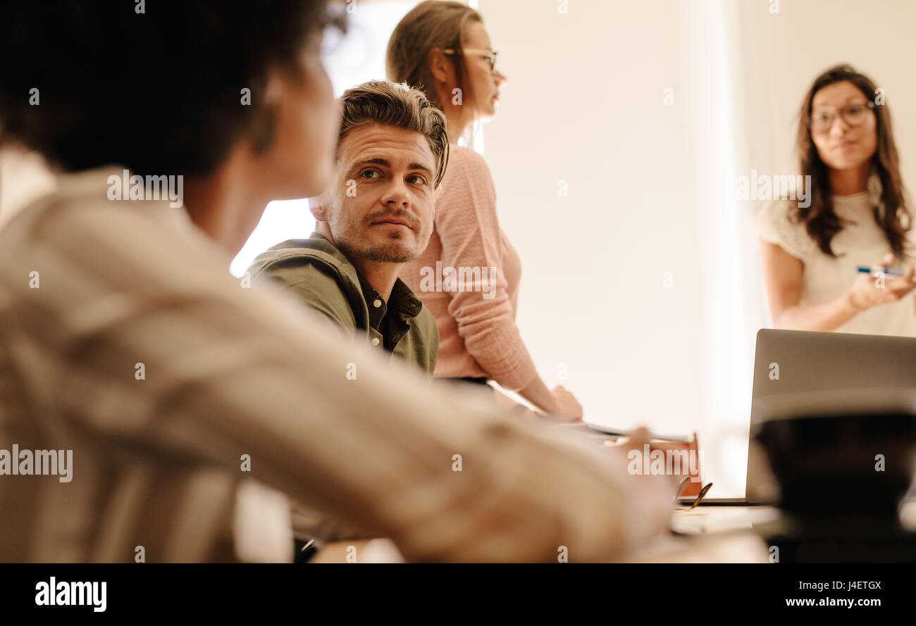 Young man during business meeting. Corporate business team meeting in conference room. - Stock Image