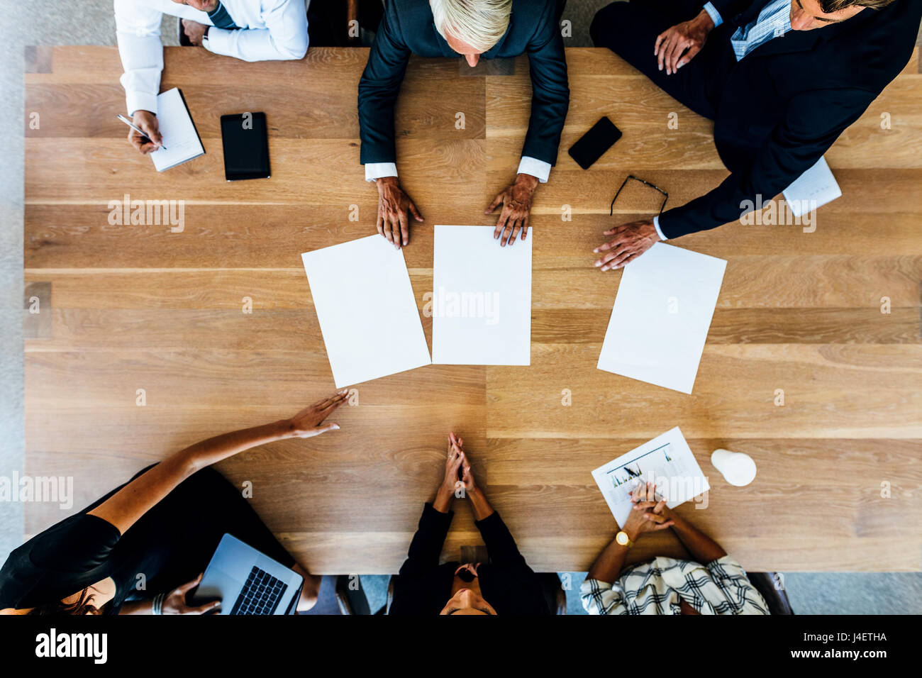 Group of people placing blank placards on table. Top view of business people having a meeting. - Stock Image