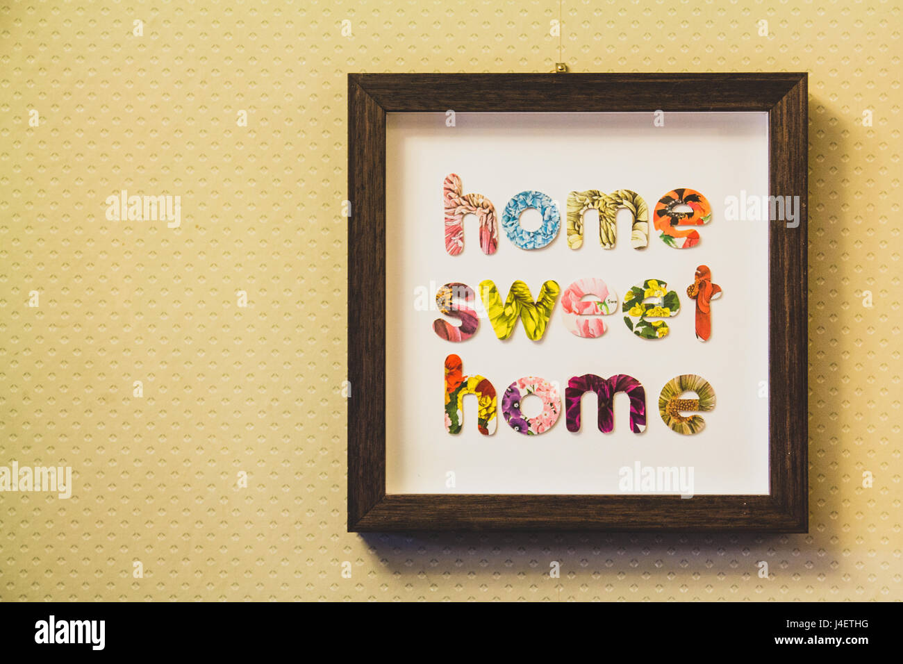 Framed letters home sweet home hung on a wall - Stock Image