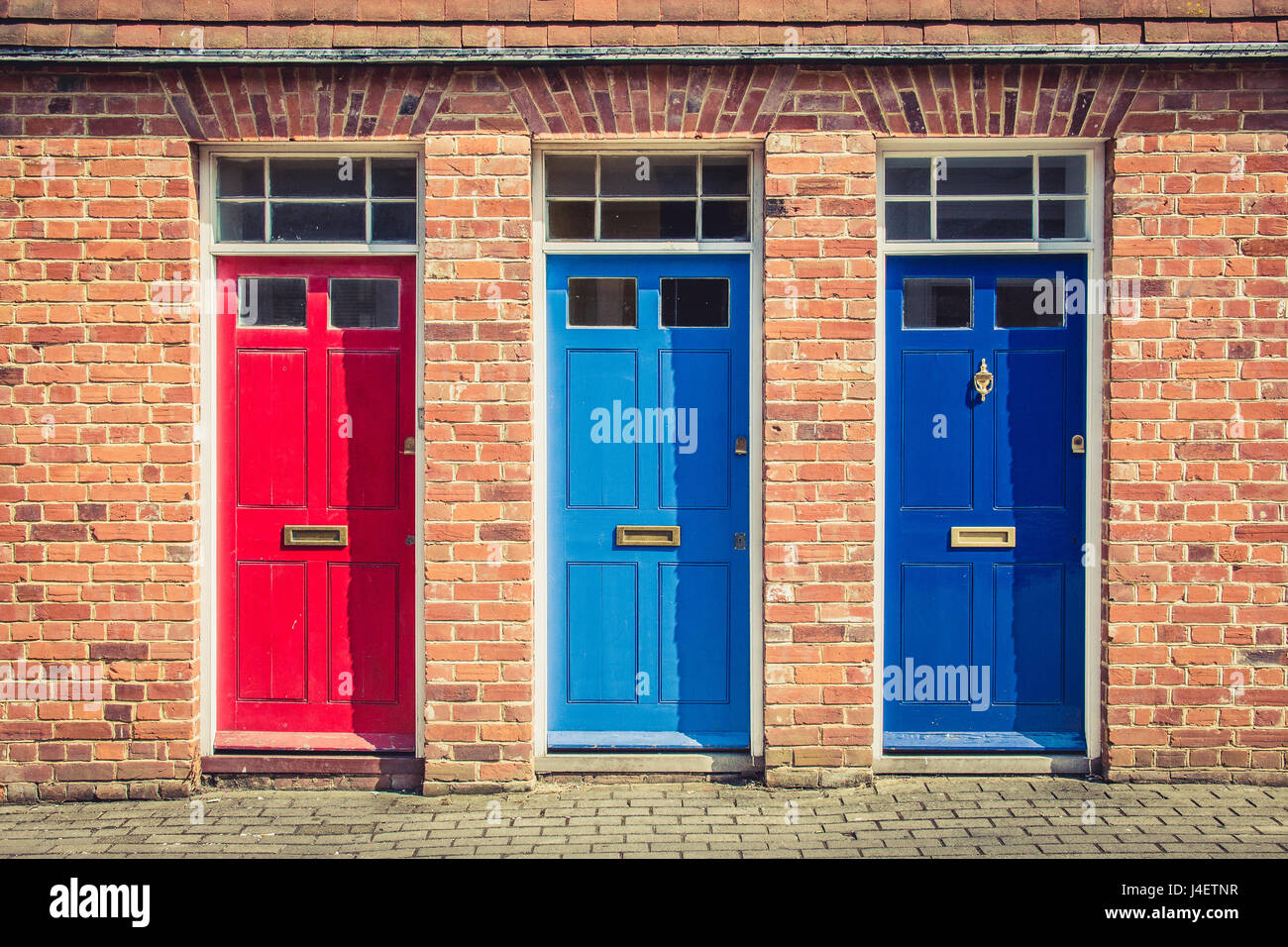 Three differently coloured front doors at the entrance of old English terraced houses. Canterbury England. & Three differently coloured front doors at the entrance of old ...