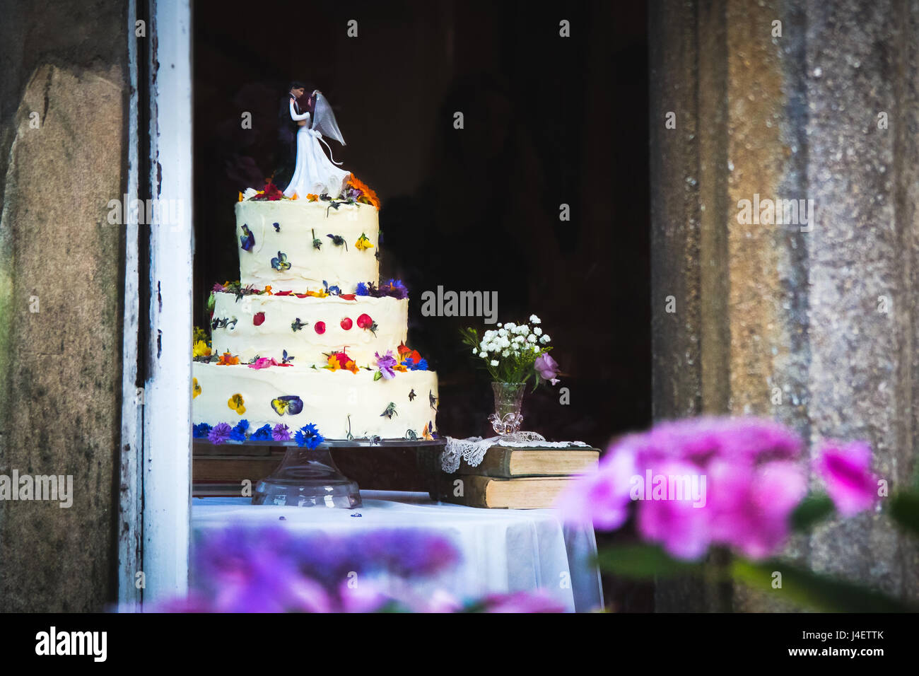 Pretty wedding cake with white icing and flowers topped with figurines of the bride and groom. Pink and purple flowers - Stock Image