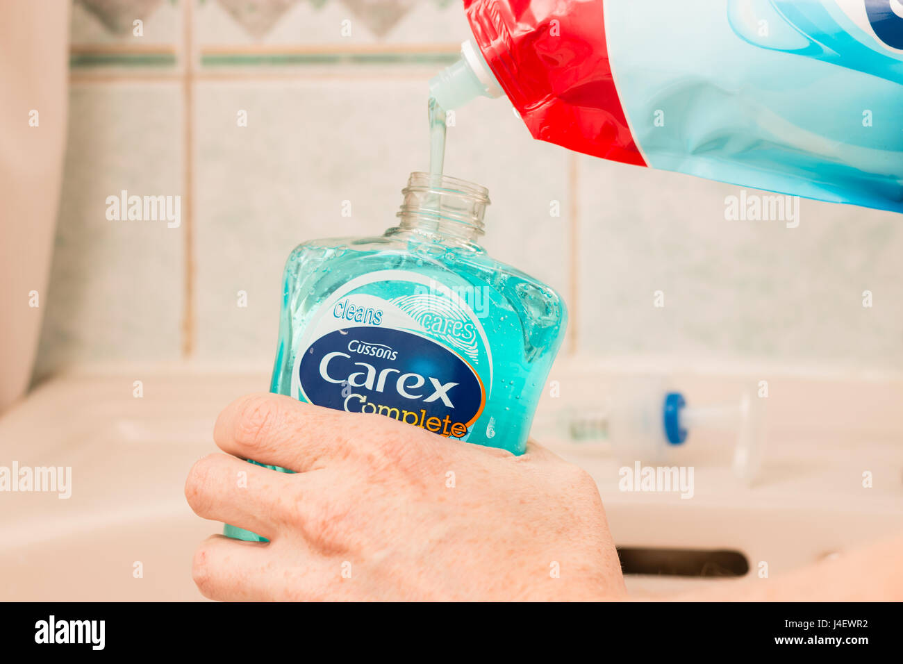 A pump action hand soap being refiled with an 'eco friendly' refill bag using 85% less plastic then buying - Stock Image