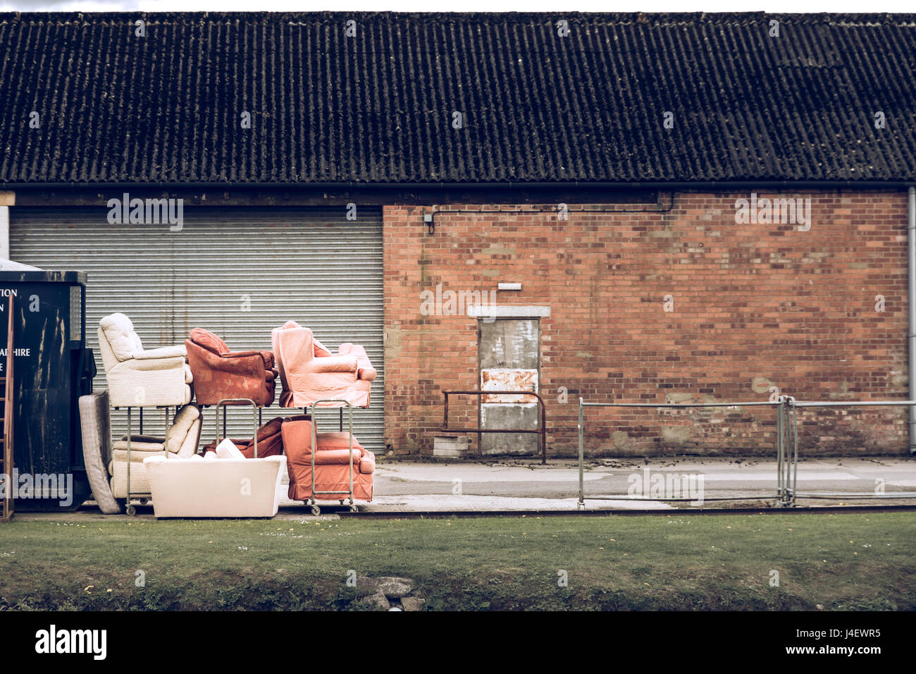 A pile of old sofas outside a warehouse - Stock Image