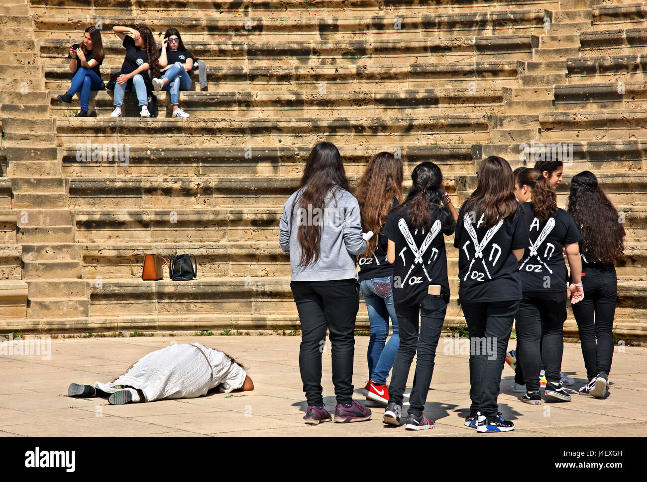 """Students, """"rehearsing"""" at the Roman Odeon in the Archaeological Park of Paphos (UNESCO World Heritage Site) Cyprus. Stock Photo"""