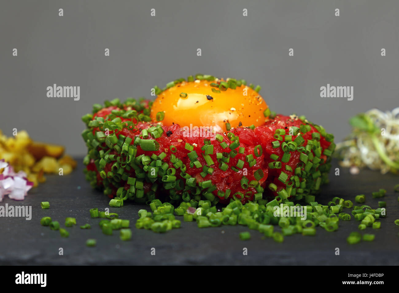 One portion of raw minced beef meat tartare steak with egg yolk ant green shallot onions served on black slate board, - Stock Image
