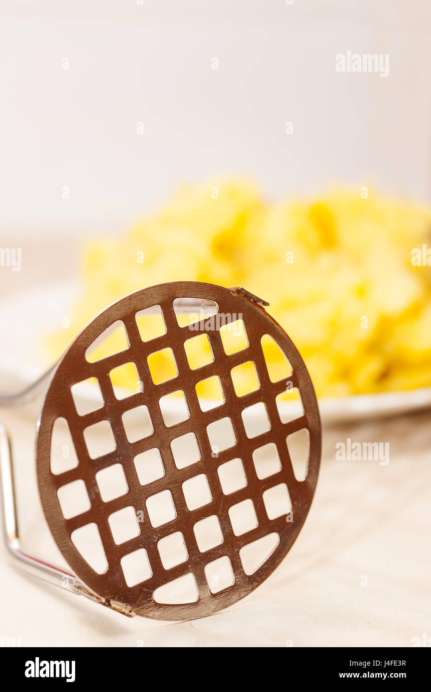 Freshly mashed potatoes in plate with masher on table - Stock Image