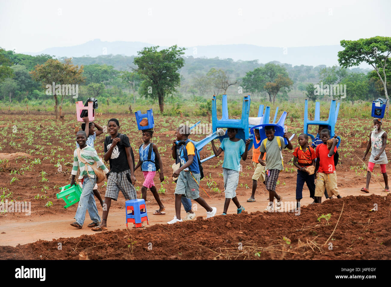 ANGOLA Kwanza Sul, village Kassombo, children on way to school, each child must bring his own plastic chair as the - Stock Image