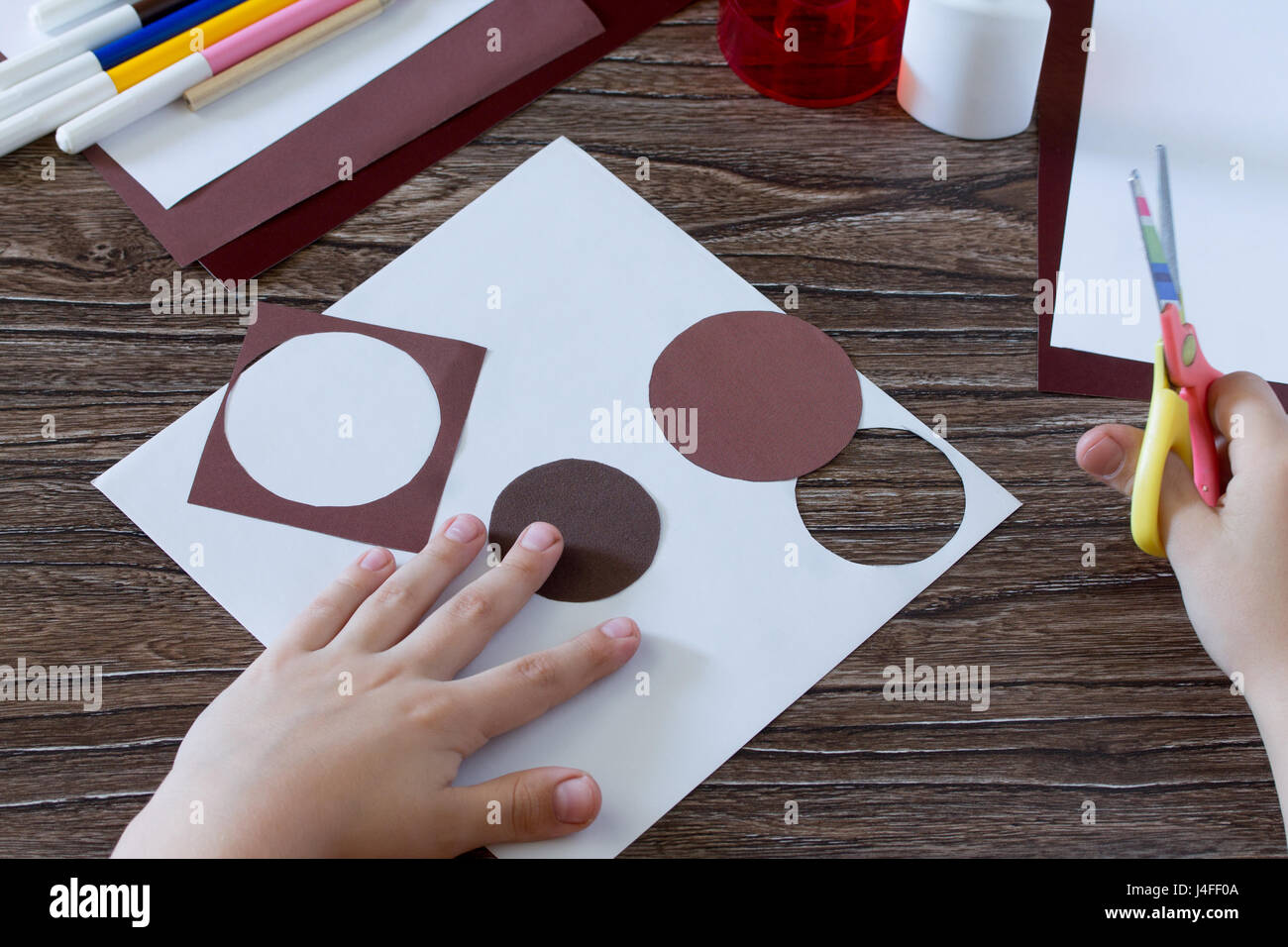 The child cuts out the details. Greeting Card guitar music. Children's art project, craft for children. Craft - Stock Image