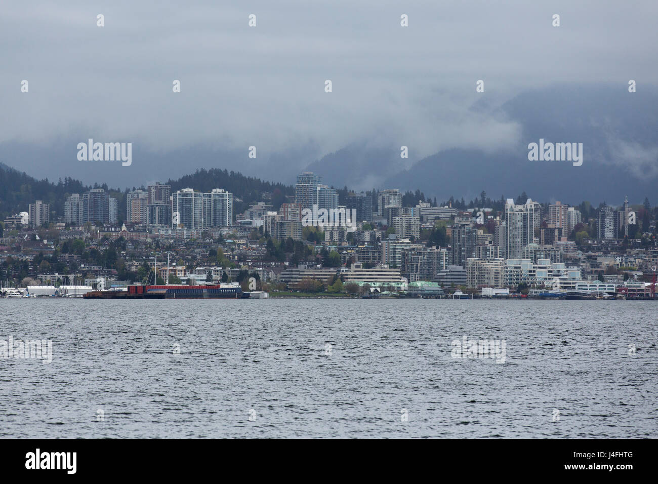 An overcast day in Vancouver, Canada. Clouds hang low over buildings in North Vancouver. - Stock Image