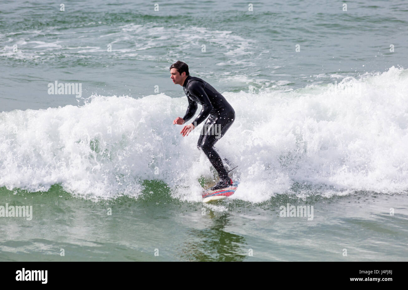 Surfer riding a wave enjoying the surf on a lovely sunny day at Bournemouth beach on Bank Holiday Monday in May Stock Photo