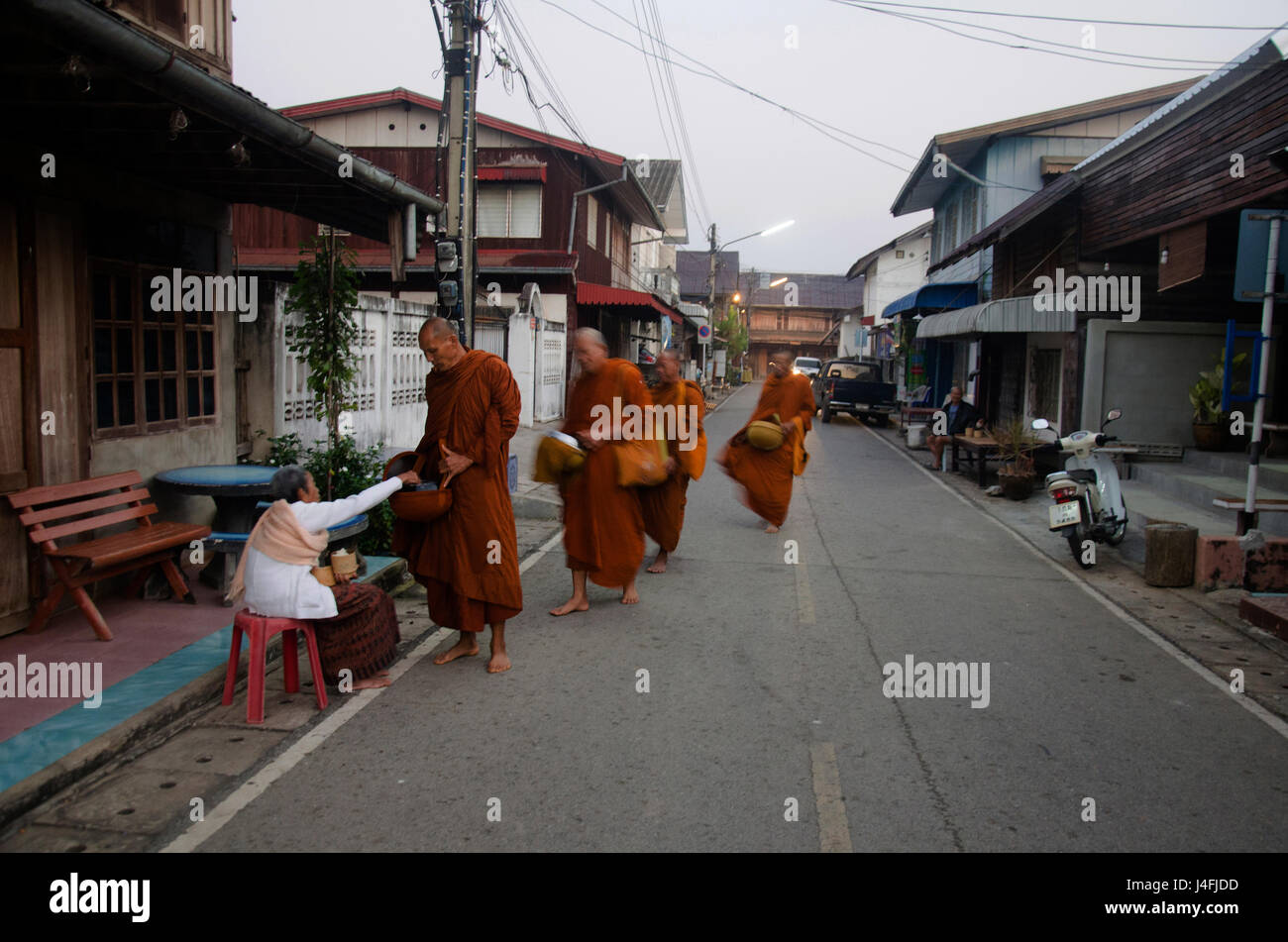 Thai people put food offerings to monks procession walk on the road of tradition of almsgiving with sticky rice Stock Photo