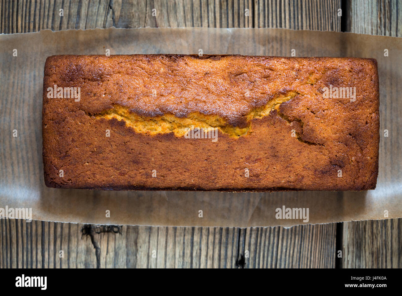 Homemade pound cake baked in a loaf pan on a wooden board  viewed from above - Stock Image