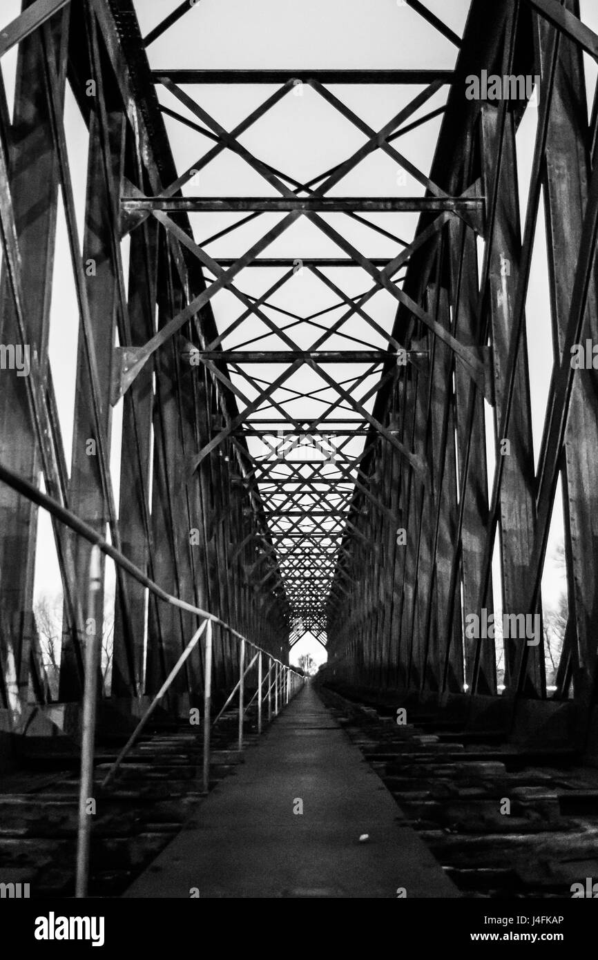 Black and white old industrial railway railroad iron bridge center perspective in night