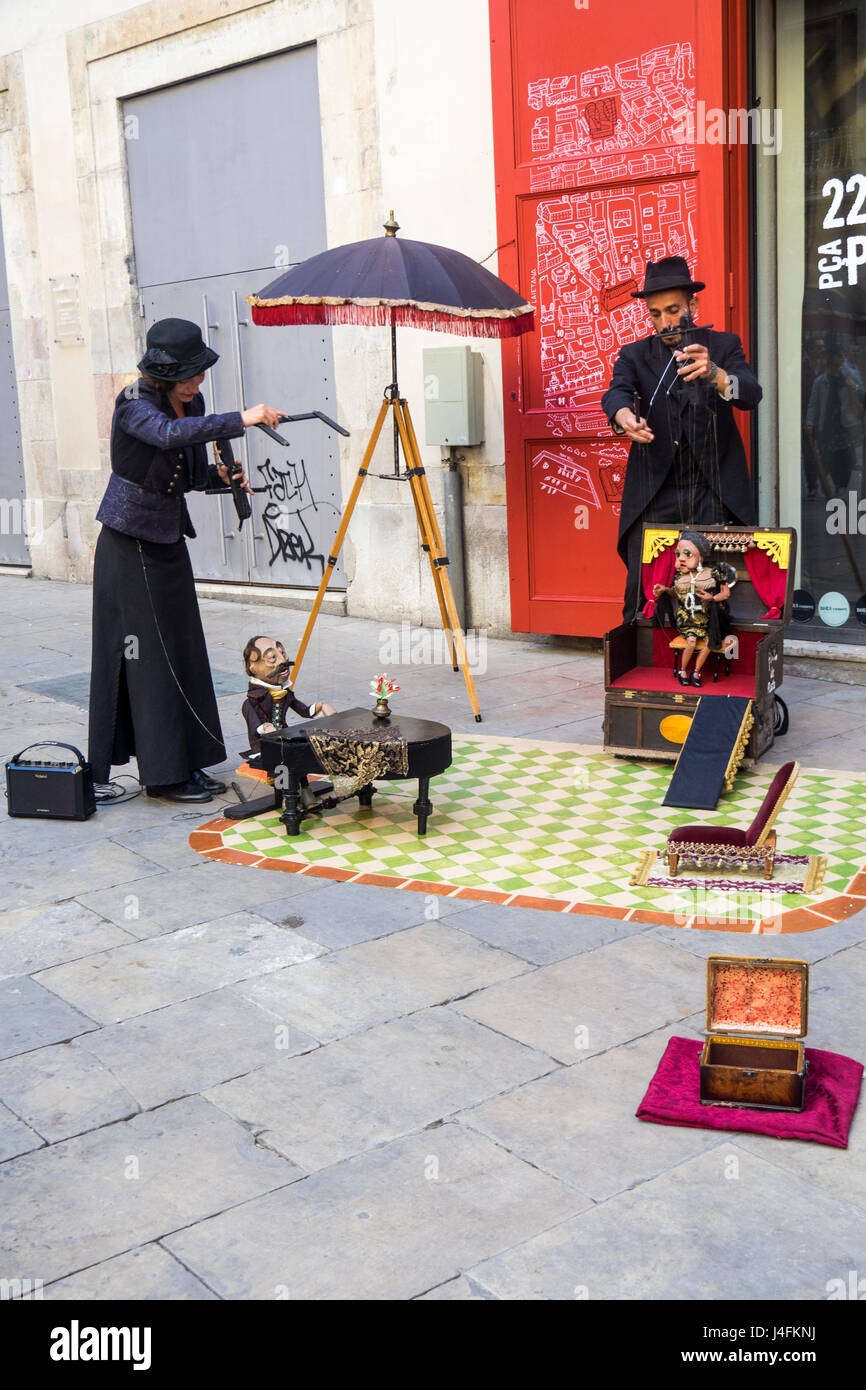 A male and female puppeteer and their marionettes performing a street theatre in the Gothic Quarter of Barcelona, - Stock Image