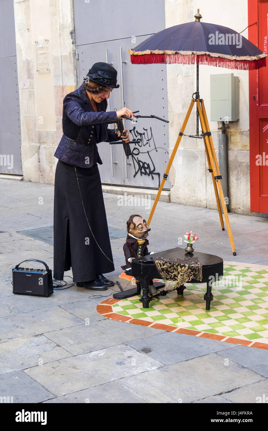 A female puppeteer and marionette performing street theatre in Passag del Born, Barcelona, Spain. - Stock Image