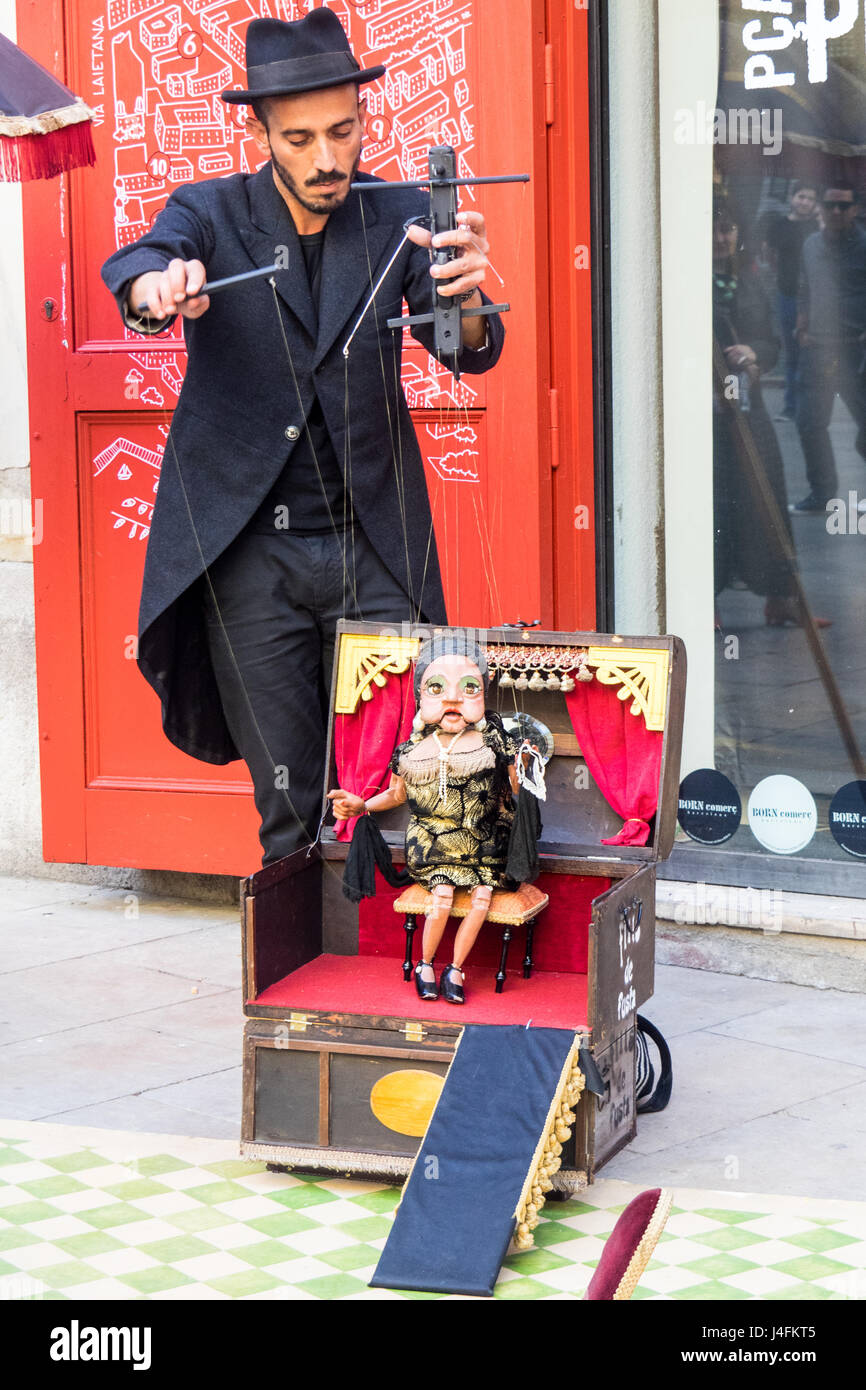 A puppeteer and marionette performing street theatre in Passag del Born, Barcelona, Spain. - Stock Image