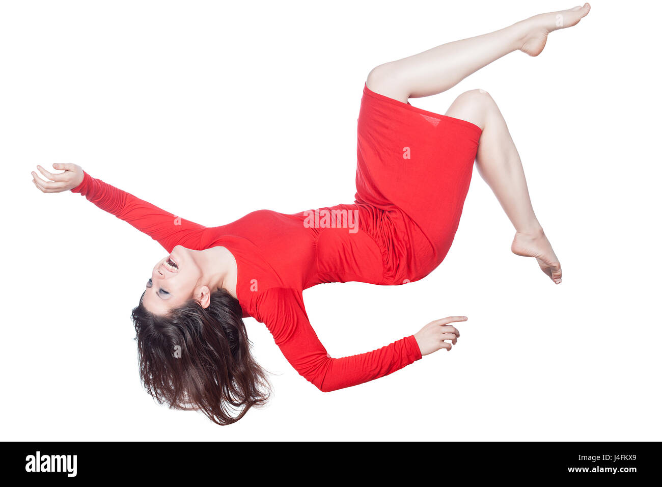 Woman in red dress floating in the air falling on a white background. - Stock Image