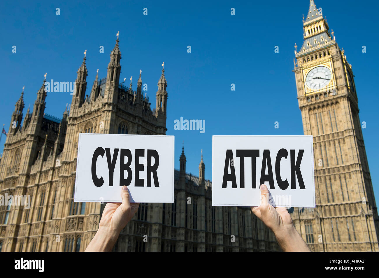 Hands holding signs protesting a computer cyber attack outside the Houses of Parliament at Westminster Palace in - Stock Image