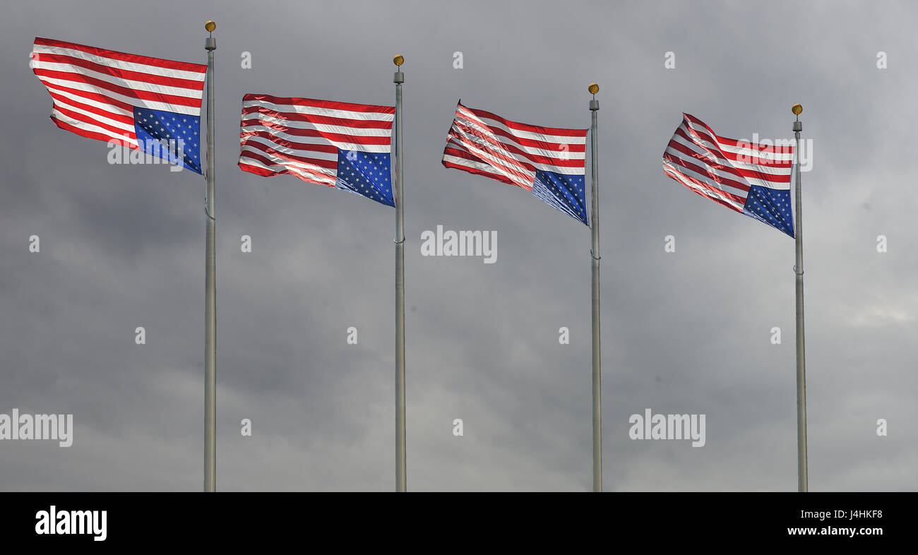 Four U.S. Flags flying upside down - signalling distress - on a windy, stormy day. - Stock Image