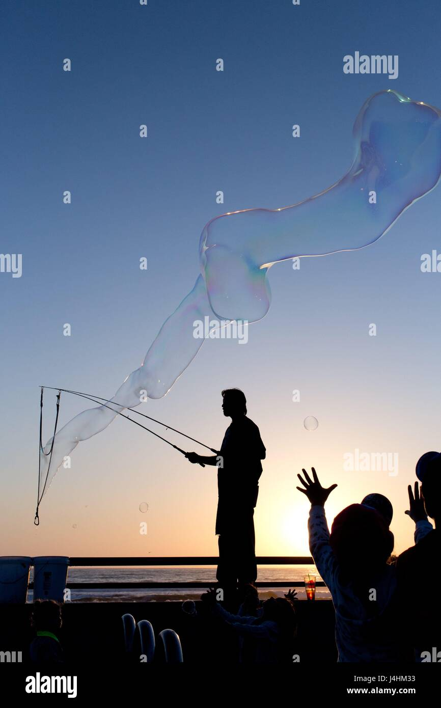 Kids at the boardwalk of Pacific Beach hunting huge soap bubbles, in March 2017. | usage worldwide - Stock Image