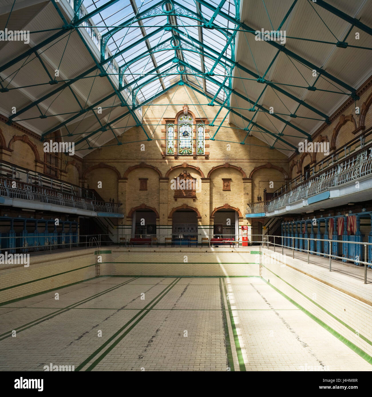 View through the swimming hall with pool before refurbishment. Victoria Baths, Manchester, United Kingdom. Architect: - Stock Image