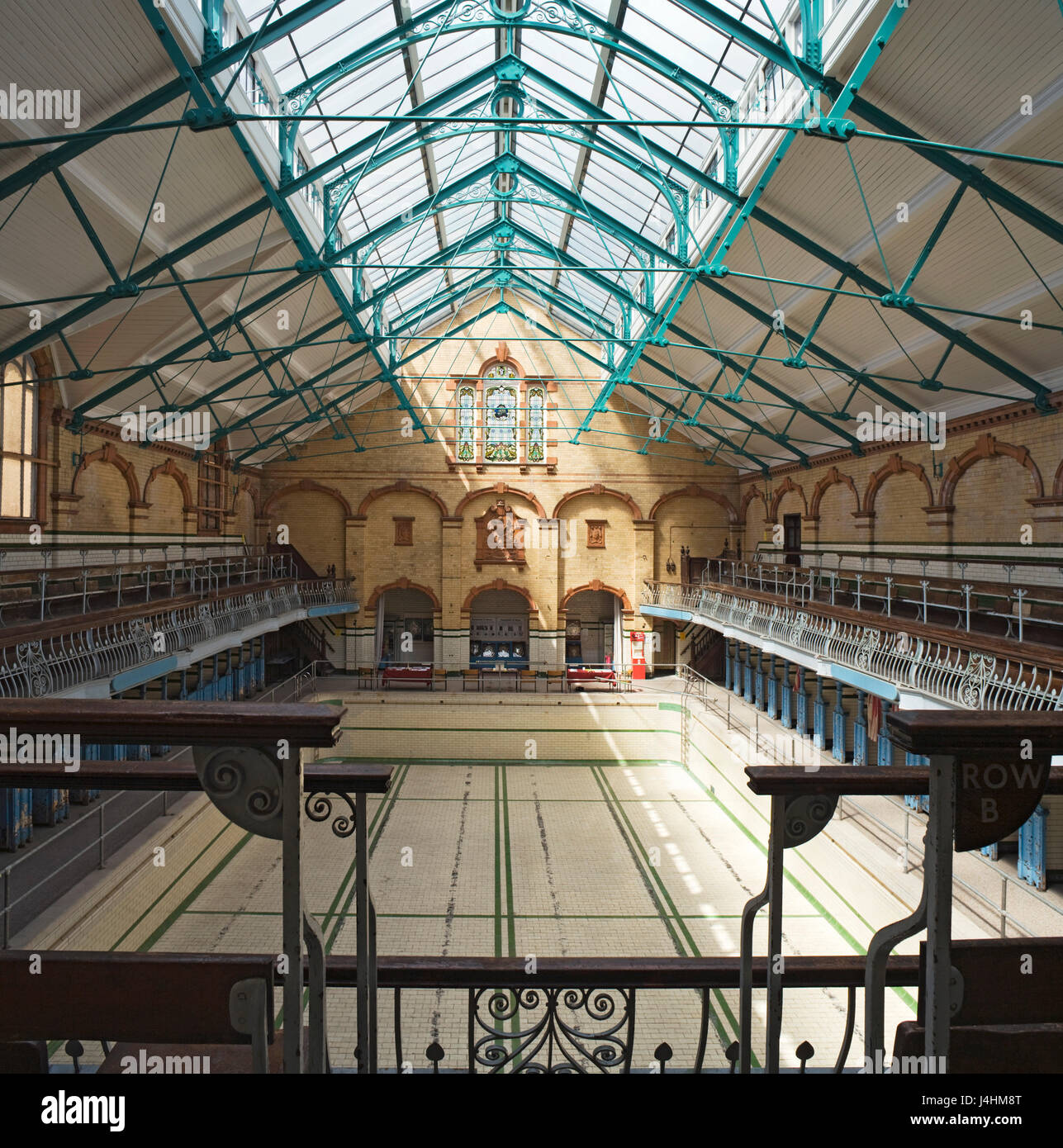 Elevated view through the swimming hall with pool before refurbishment. Victoria Baths, Manchester, United Kingdom. - Stock Image