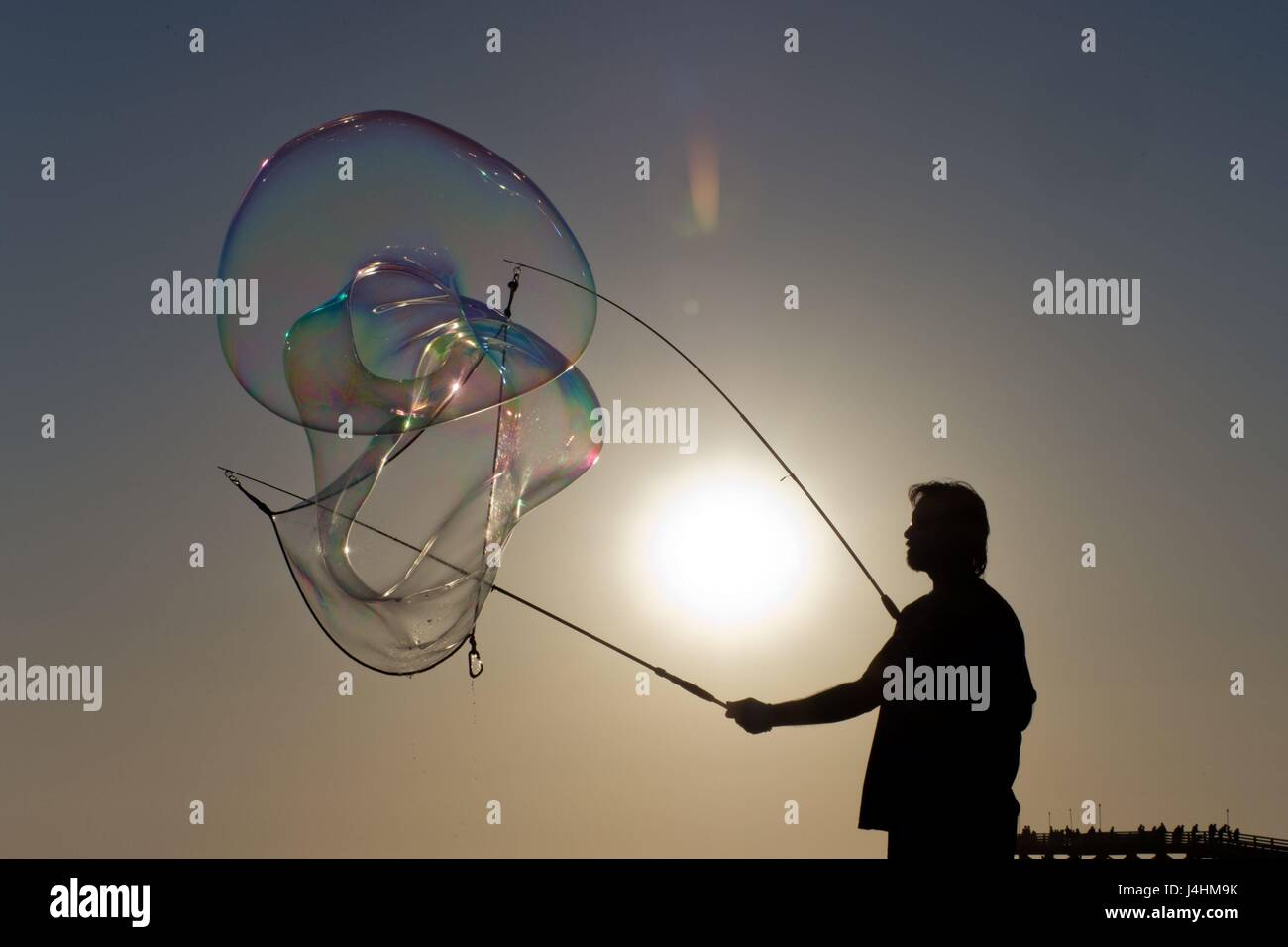Man at the boardwalk of Pacific Beach creating huge soap bubbles, in March 2017. | usage worldwide - Stock Image