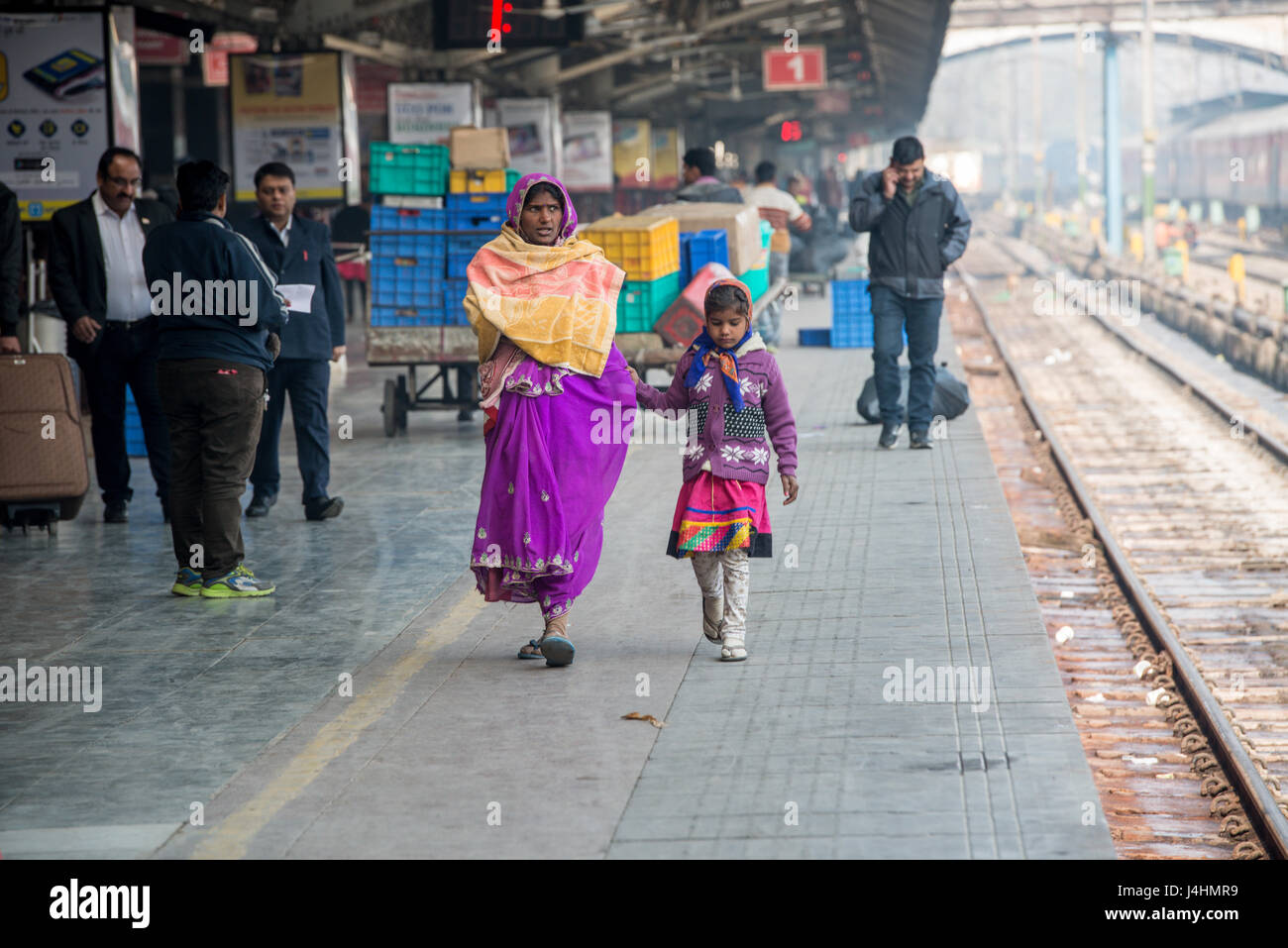 A mother and daughter walk down a train platform at a station in New Delhi, India. - Stock Image