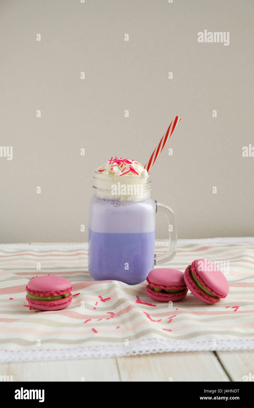 Purple coffee in stylized mason jar cup with macarons and colorful decoration. Blueberry milk shake. Unicorn coffee. - Stock Image