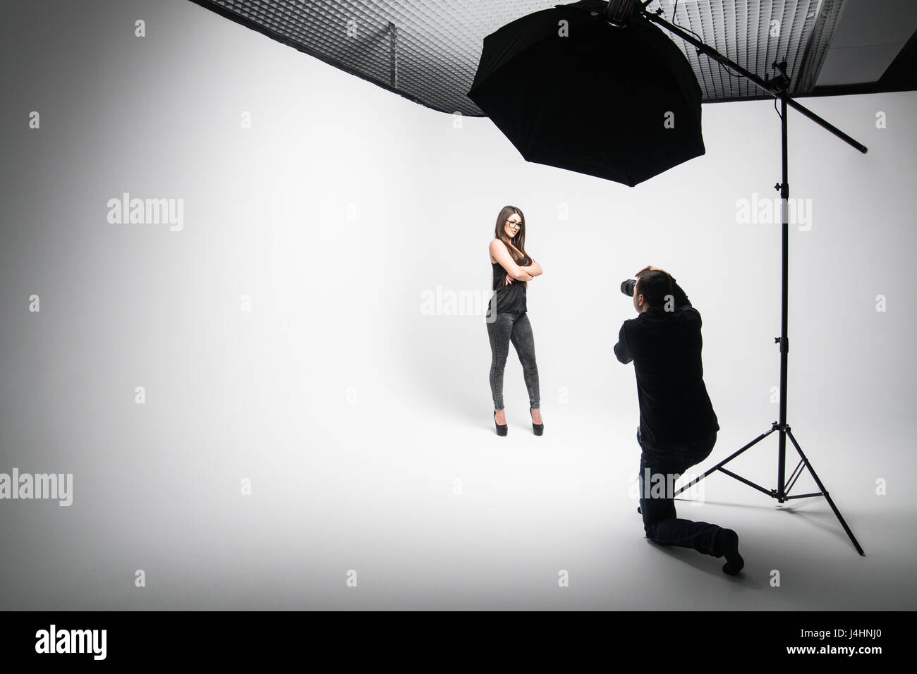 Girl the photographer takes pictures of model in black on a white background in Studio Stock Photo