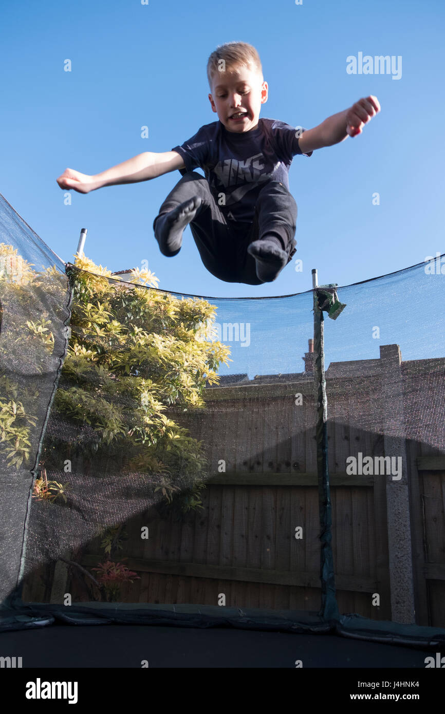 Young boy having fun bouncing on a trampoline in his garden - Stock Image