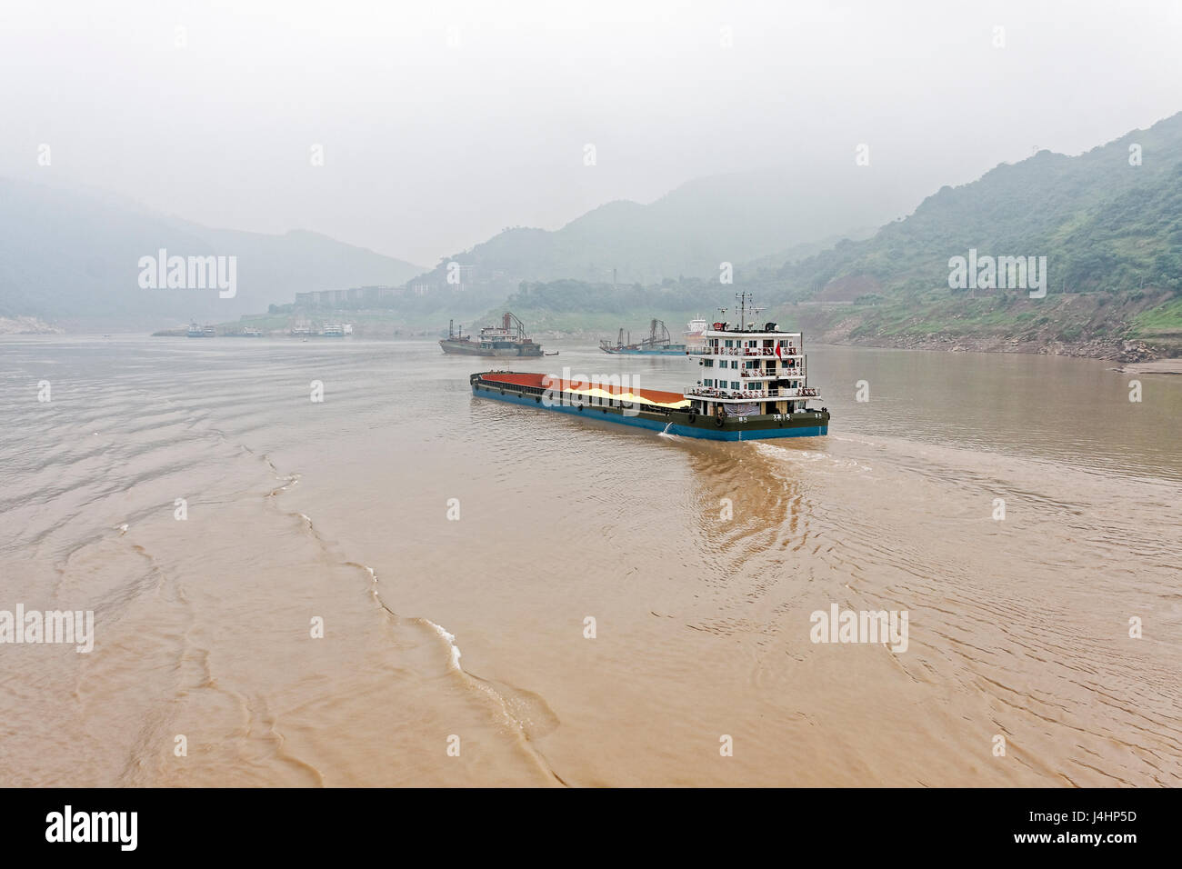 Cargo ships laden with minerals make their way up the Yangtze River between steep wooded hills shrouded in mist - Stock Image