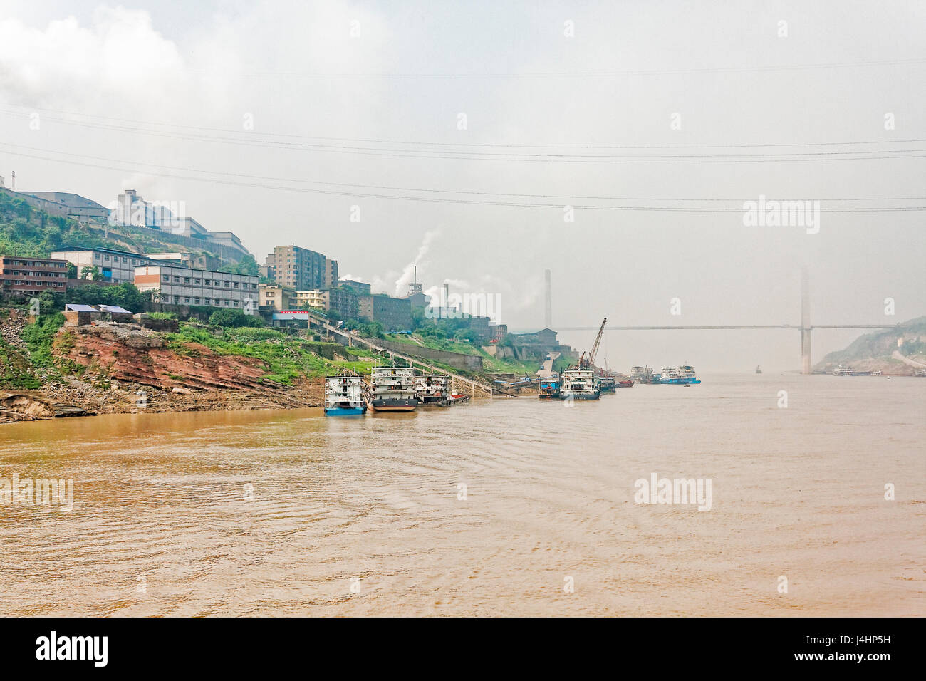 Ships moored close to a large manufacturing facility on the banks of the Yangtze River, near the town of Fuling, - Stock Image