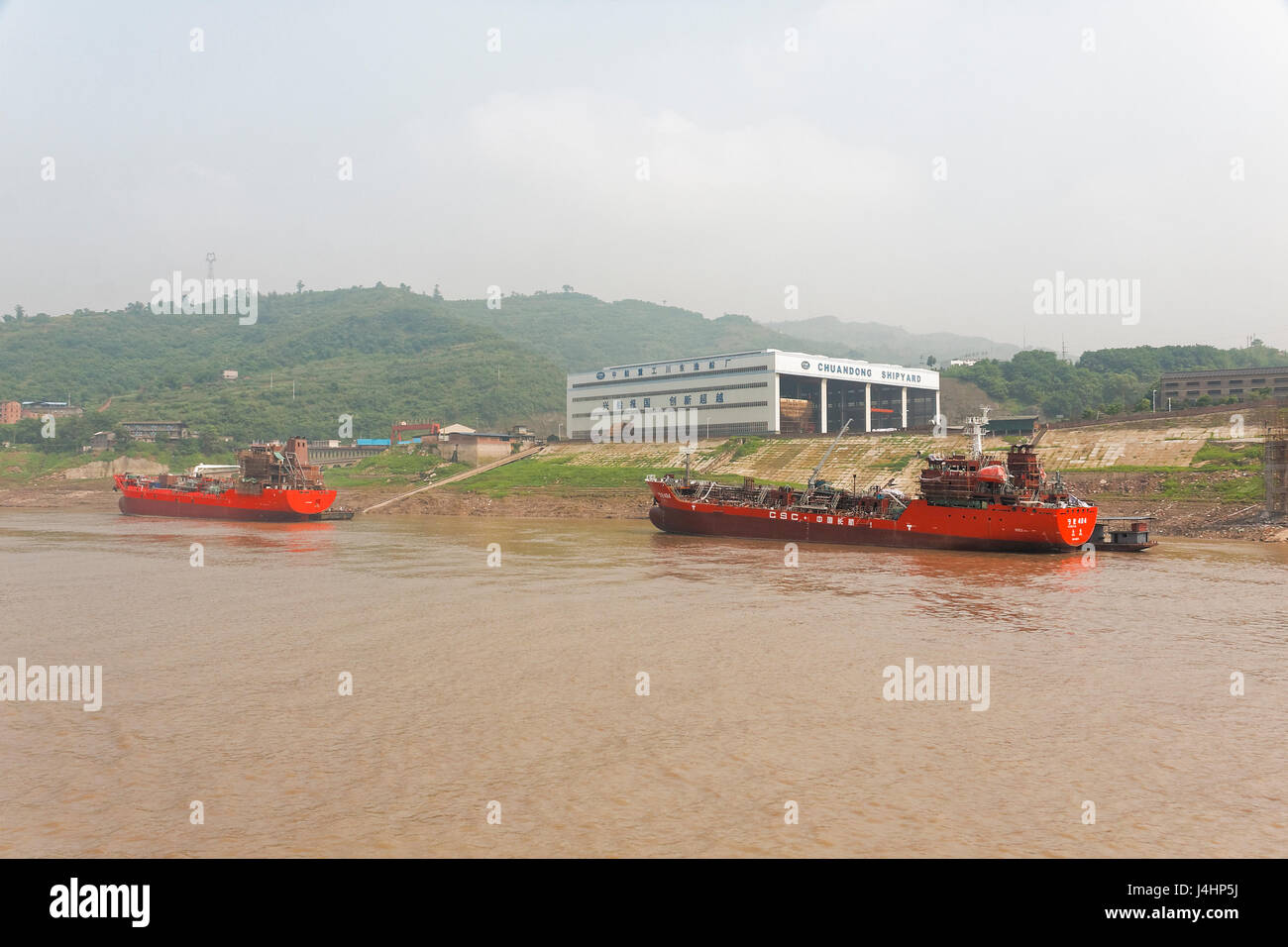On the banks of the Yangtze River, near Fuling, there is a shipyard with a large shed, slipway and two new ships - Stock Image