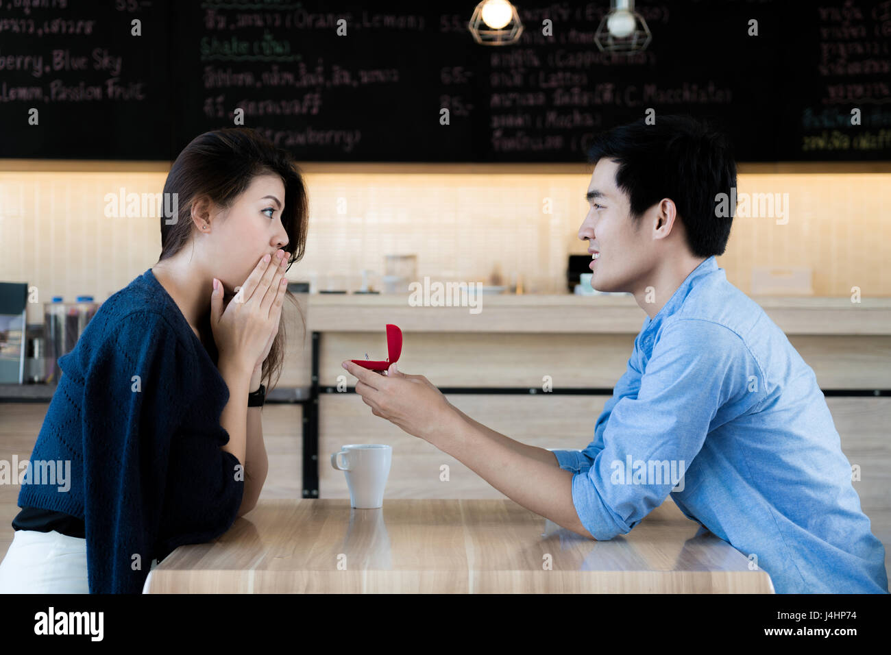 Asian man showing an engagement ring diamond to his amazed girlfriend in a restaurant. Proposal concept - Stock Image