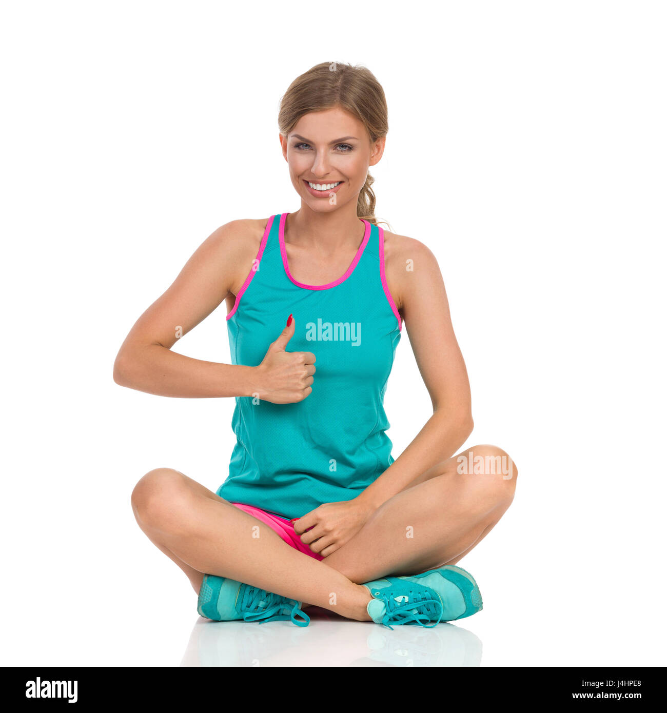 Beautiful smiling young woman in vibrant sports clothes sitting on a floor with legs crossed, showing thumb up and - Stock Image