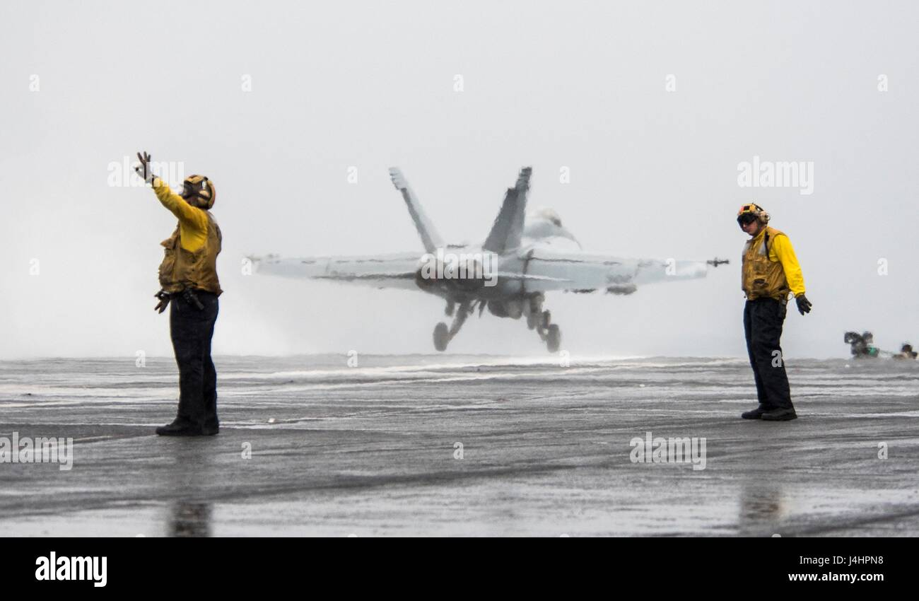 A USN F/A-18E Super Hornet jet fighter aircraft launches from the flight deck aboard the USN Nimitz-class aircraft - Stock Image