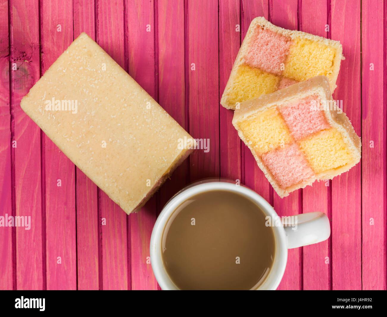Almond Flavoured Battenberg Sponge Cake Against a Pink Background - Stock Image