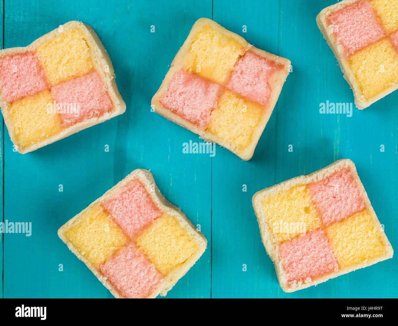 Almond Flavoured Battenberg Sponge Cake Against a Blue Background - Stock Image
