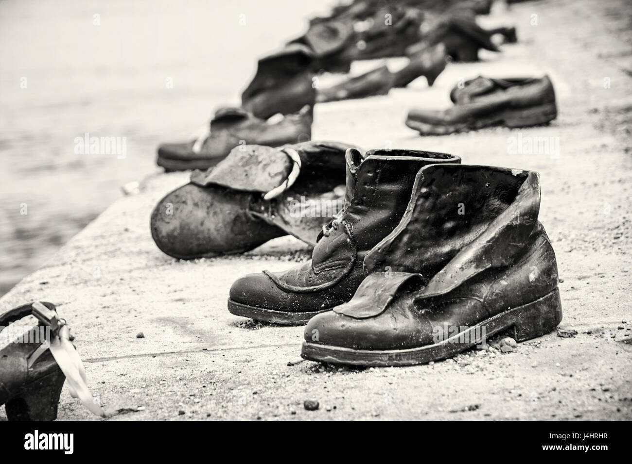 Shoes monument on the Danube bank is a memorial in Budapest, Hungary. Place of reverence. Black and white photo. - Stock Image